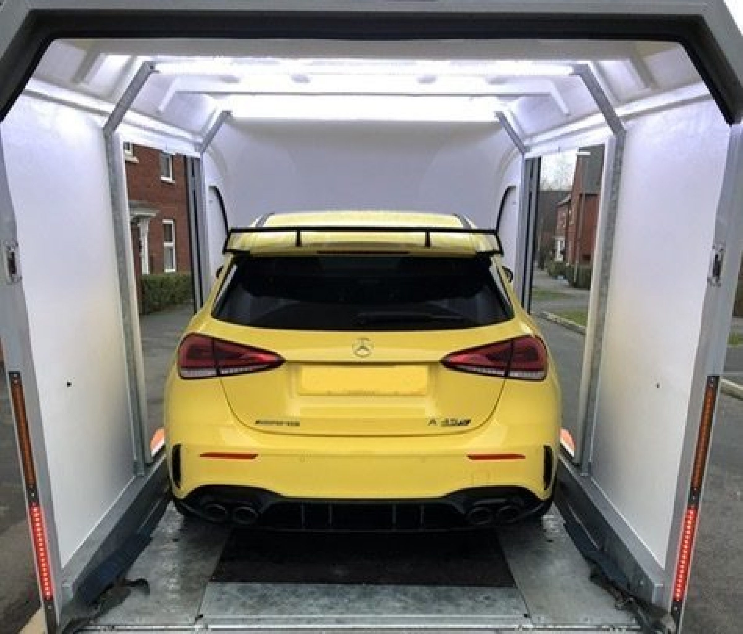 New car delivered in enclosed trailer